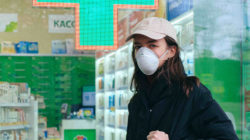 Woman in front of chemist's with mask and cap, wearing a black coat and carrying a black bag