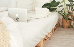 Bed made from pallets with Mac laptop, white bed linen and plant